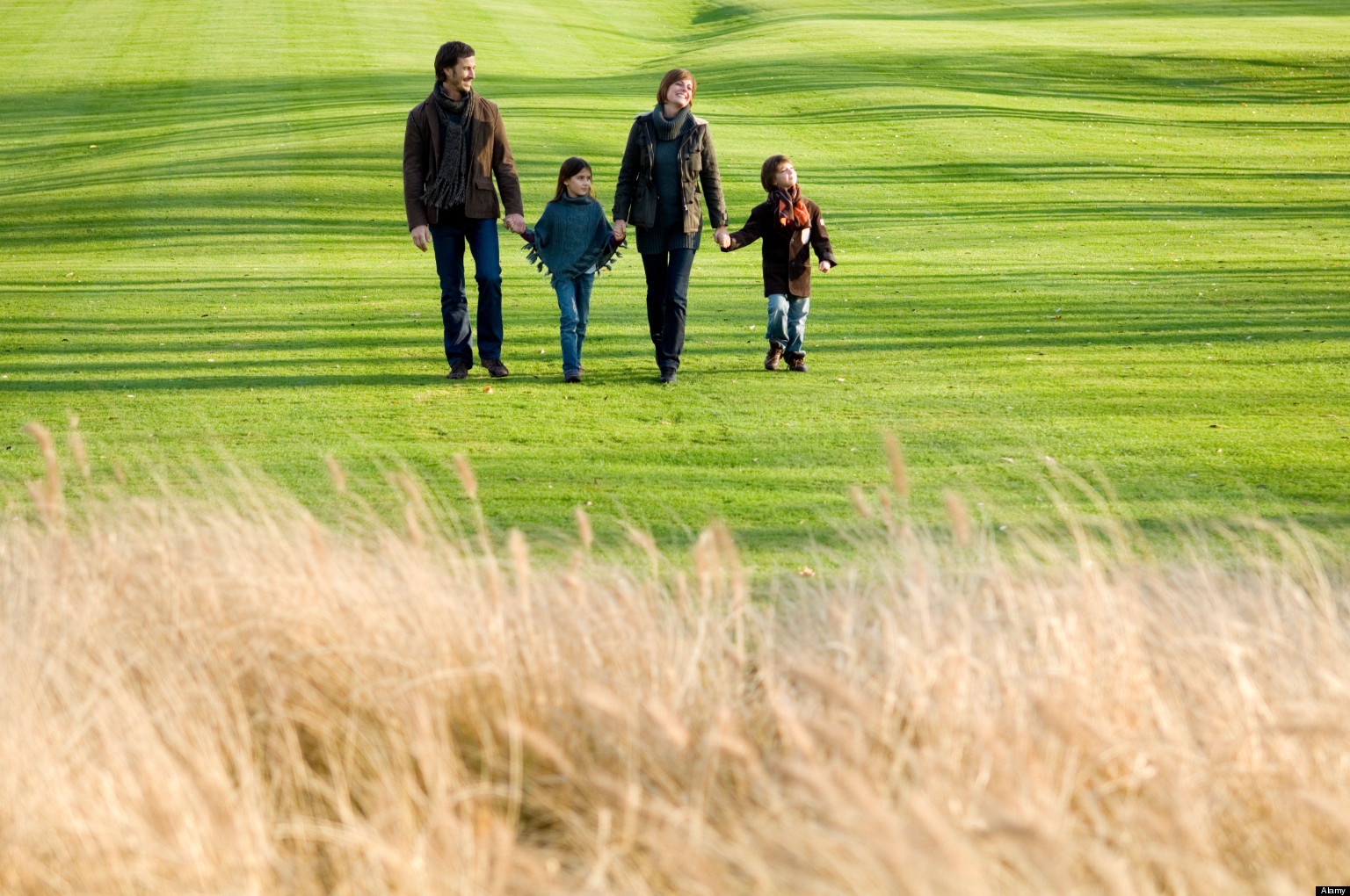 Two children with their parents walking in a park